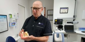 Dr Finkelstein holding Dental implants model