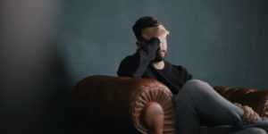 Man on a leather lounge holding his head