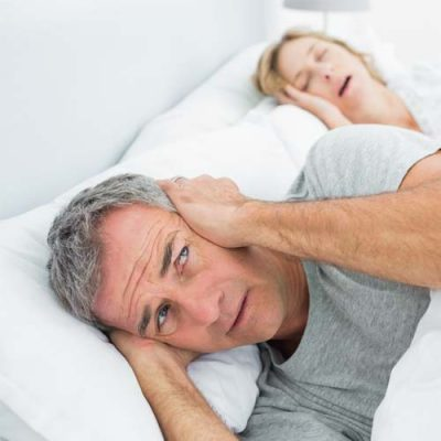 A man having trouble sleeping while his partner is snoring due to her sleep apnea